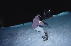 "A remarkable discovery! A ""snowboarder"" surfs down the brightly lit slopes of Pats Peak on a winter's night. (Pats Peak photo)"