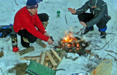 Warmth in the wilderness. With plenty of firewood and steaks to cook, David Shedd and Matt Marean can enjoy a warm refuge on a chilly winter backpacking trip. (Tim Jones photo)
