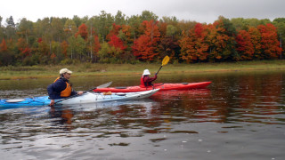 Leo Freeman and Marilyn Donnelly paddle past a spectacular foliage display on the Aroostook River near Presque Isle, Maine. (Tim Jones/EasternSlopes.com)