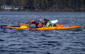 Student Amy Fullerton assists instructor Vaughan Smith as he demonstrates how to get back into a kayak after a wet exit. (EasternSlopes.com)