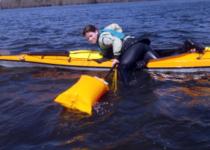 Student Amy Fullerton  practices using an inflatable paddle float and a rope sling to get back into her sea kayak. This is a skill you want to practice before you need it! (EasternSlopes.com)