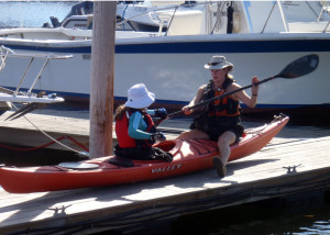 A good kayak instructor gets up close and personal. Here Theresa Willette of Coastal Maine Kayak helps student Marilyn Donnelly with her paddle technique. (EasternSlopes.com)