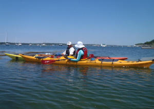 A sea kayaking lesson can translate easily into a lovely day on the water. At the start of an overnight camping adventure on the Maine cost, trip leader Cathy Piffath of H2O Outfitters helps Marilyn Donnelly strethen her paddling skills. (EasternSlopes.com)