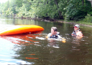 Student Nancy Larson was (understandably) nervous about intentionally flipping her boat to practice how to safely exit an upside-down kayak. It was somewhat easier in shallow water with instructor Jeff Brent of Contoocook River canoe Company ready to help. (EasternSlopes.com)