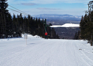 Riding the T-bar at Saddleback Maine. The sun is on your face and the cold north wind is behind you as you ride up on a day when other lifts are on wind hold. (Tim Jones/EasternSlopes.com)
