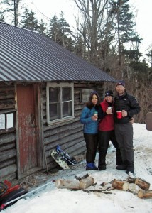 All smiles. In the morning it was as warm outside the cabin as it was inside. Nobody was willing to put down their hot coffee to pose for a photo! (EasternSlopes.com)