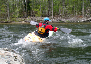 "Zoar instructor Ben Natusch demonstrates how to lean the boat and ""peel out"" of an eddy behind a big rock in fast current. (EasternSlopes.com)"